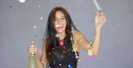 vivacious: Laughing vivacious woman celebrating the New year with falling confetti  streamers and a magnum of champagne  studio over grey