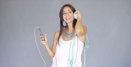 chicas bailando: Young woman listening to music on her headphones at New Year as she celebrates with party streamers around her shoulders and a happy smile
