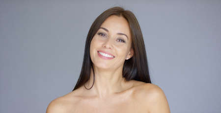 bare women: Single gorgeous young adult female with bare shoulders over gray background with copy space