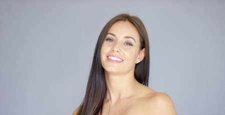 Single gorgeous young adult woman in long brown hair with pleasing smile over gray background Stock Photo