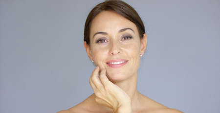 Front view on cute single young adult woman with eyes closed and hands on cheeks over gray background with copy space Stock Photo