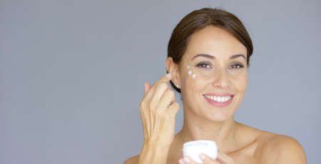 Beauty portrait of a smiling young brunette woman applying dabs of face cream or moisturizer to her face on the cheek bone  over grey Banque d'images