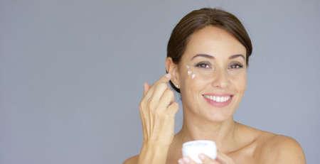 Retrato de la belleza de una mujer joven morena sonriente aplicar toques de crema para la cara o crema hidratante para la cara en el hueso de la mejilla sobre gris Foto de archivo