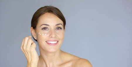 eye cream: Beauty portrait of a smiling young brunette woman applying dabs of face cream or moisturizer to her face on the cheek bone  over grey Stock Photo