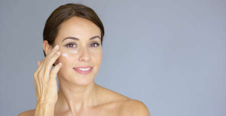 eye cream: Beautiful young woman applying face cream to her cheek bone in a beauty  skincare or cosmetics concept  on grey with copy space