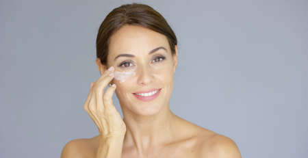 woman eye: Gorgeous young woman applying face cream to her cheek with her fingertips with a smile in a skincare and beauty concept  close up head and shoulders over grey.