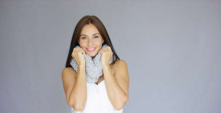 warm shirt: Beautiful and sexy woman posing with woolen scarf around her neck. She smiling to the camera while isolated on gray background.