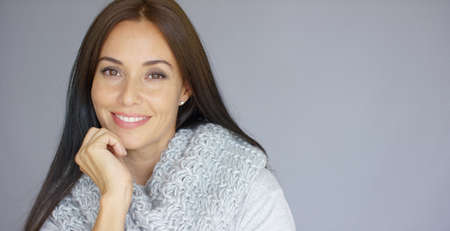 Elegant beautiful middle aged woman posing with woolen warm scarf around her neck. She smiling and trying to warm up herself. Isolated on gray background.