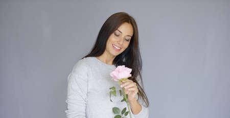 mujer con rosas: Midlle edad largo de la mujer, de pelo largo, elegante y hermosa que sostiene y oler rosa flor rosa. Ella está aislada sobre fondo gris.
