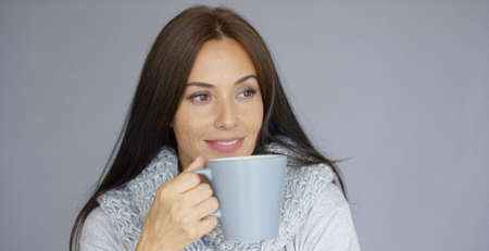 gir: Beautiful long haired, brunette woman holding in her hand cup of hot drink. She wearing woolen scarf around her neck. She trying to warm up herself. Isolated on gray background.