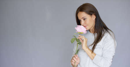 Midlle aged, long haired, elegant and beautiful woman holding and smell pink rose flower. She is isolated on gray background. Stock Photo