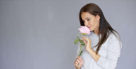 olfato: Midlle edad largo de la mujer, de pelo largo, elegante y hermosa que sostiene y oler rosa flor rosa. Ella está aislada sobre fondo gris.
