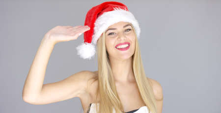 sexy young girls: Pretty young girl doing hello hand gesture. She wearing Santa Claus red hat. Smiling and looking to the camera.