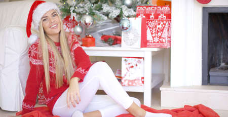 young tree: Beautiful sexy girl sitting on the floor next to Christmas tree and fireplace at her living room. She wearing Santa Claus hat white leggings and winter woolen sweater. Smiling Stock Photo