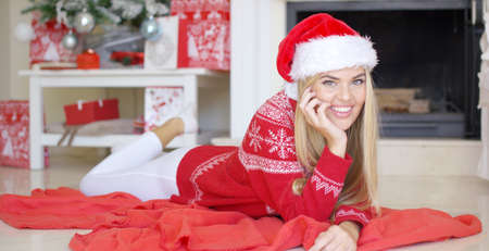 young tree: Young happy girl lying on red blanket next to fireplace and christmas tree in her living room. She looking at camera and enjoys christmas time in her family home. Wearing Santa Claus hat