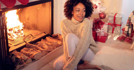 women sitting: Woman seated by fireplace and holiday setting and wearing warm woolen sweater and white leggings. She has Christmas tree behind her back. Stock Photo