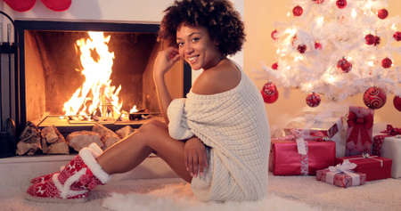 Cute young woman warming herself at the fire in festive red booties in front of the Christmas tree sitting on the floor looking at the camera with a smile.