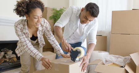 taping: Couple taping boxes as they pack up their home Stock Photo