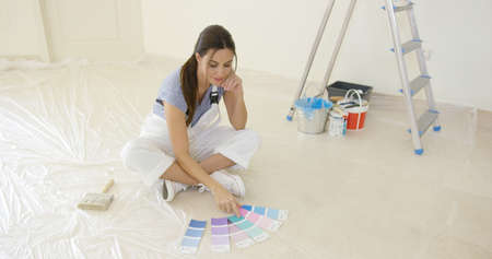 decorating: Young woman renovating or decorating her new home Stock Photo