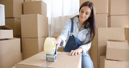 moving: Young woman moving home packing boxes Stock Photo