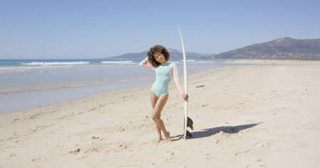 Female posing on beach with surfboard Stock Photo