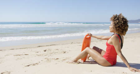 patrolling: Female with rescue float sitting on beach Stock Photo