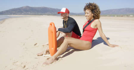 patrolling: Male and female lifeguards sitting on beach