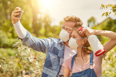 Male and female professional gardeners posing for selfie with sprayers and respirators while fertilizing plants in hothouse. Stock Photo