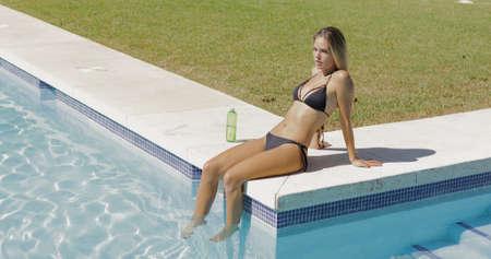 Jonge blonde in zwarte bikini ontspannen aan kant van zwembad opknoping benen in verfrissende water en wegkijken dromerig. Stockfoto