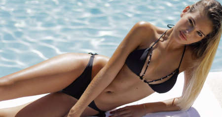 Young woman with fit body posing sexually in black bikini lying on poolside and looking seductively at camera on background of blue water.