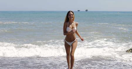 Young cheerful model in white bikini running sexually on beach looking at camera on background of white and blue water of sea.