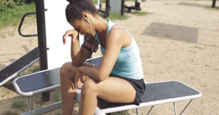 Fit ethnic woman in sportswear looking exhausted while having rest on bench in street gym keeping eyes closed and moping her brows.