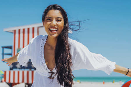 Young excited girl in white dress laughing happily at camera having fun on sunny tropical beach on background of blue sky.