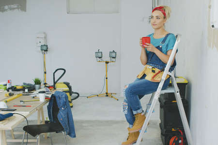 Attractive young blond woman in jeans overalls, tool belt and red headband sitting relaxed on stepladder holding red mug with drink and looking away dreamily at unpainted wall and workbench