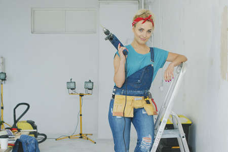 Beautiful blond young female in jeans overalls and red headband standing relaxed leaning on stepladder holding electric drill and looking at camera smiling with unpainted wall and workbench nearby. Stock Photo
