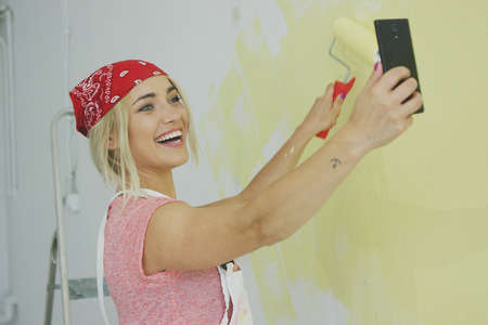 Gorgeous smiling young female in red bandana painting wall with roller and taking photo on smartphone front camera Stock Photo