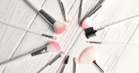 From above view of makeup brushes of different kind laid in circle on wooden background Stock Photo