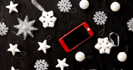 From above view of white Christmas decorations and red mobile phone on wooden background Stock Photo