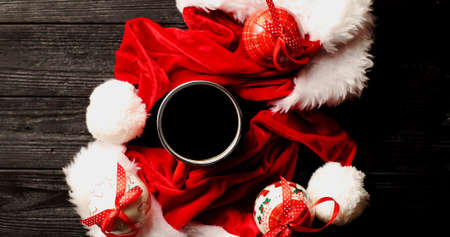 From above view of cup of coffee surrounded by red Christmas hats and decorative balls on wooden background