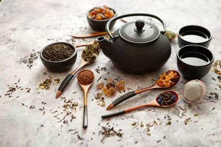 IJzeren vintage theepot en kopjes. Gedroogde verschillende soorten thee op houten lepels. Stenen achtergrond met kopie ruimte