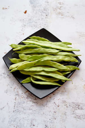Black ceramic plate with fresh green bean pods placed on white rusty table. Top view shot with copy space.