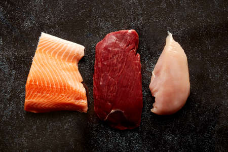 Fresh raw beef steak, chicken breast, and salmon fillet. Top view composition on dark rusty background.