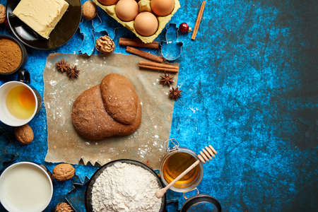 Ready for next step raw gingerbread dough placed among various ingredients. Christmas baking concept. Placed on blue background. View from above.
