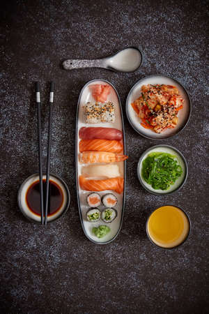 Asian food assortment. Various sushi rolls placed on ceramic plates. Kimchi and goma wakame salads. Soy souce and chopsticks on sides. Grungy dark background with copy space.