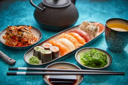 Various sushi rolls placed on ceramic plates. Traditional iron tea pot and green tea in cup. Kimchi and goma wakame salads. Soy souce and chopsticks on sides. Blue background.