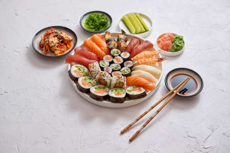 Asian food assortment. Various sushi rolls placed on round ceramic plate. Kimchi and goma wakame salads, fresh cucomber, ginger and wasabi. Soy souce and chopsticks on sides.