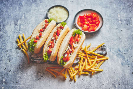 Assortment of three tasety hot dogs, placed on wooden cutting board. Served with french fries, onion and tomato. View from above. Stone background.