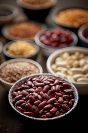 Raw red bean in ceramic bowl. Composition of superfoods in background. Placed on dark rusty table. Selective focus. Zdjęcie Seryjne