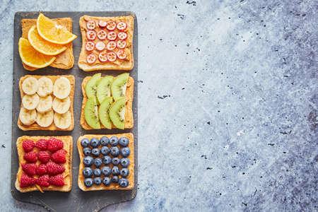 Seis tostadas saludables para el desayuno. Rebanadas de pan integral con mantequilla de maní y diversas frutas. Servido en tabla de cortar gris. Vista superior, fondo de piedra gris. Concepto de dieta con espacio cpoy.