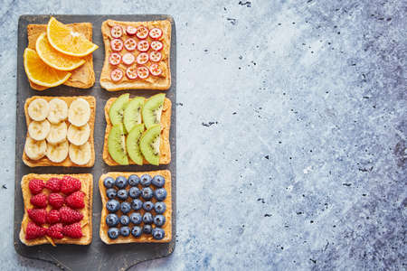 Six Healthy breakfast toasts. Wholegrain bread slices with peanut butter and various fruits. Served on grey cutting board. Top view, grey stone background. Dieting concept with cpoy space Standard-Bild
